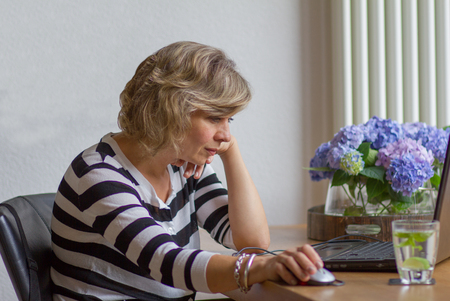Aantrekkelijke vrouw van middelbare leeftijd te kijken met belangstelling naar de monitor Stockfoto