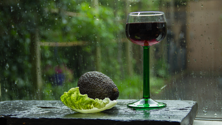 Summer sensation. Fresh rain in the garden outside, avocado, salad, and a glass of wine on the windowsill Stock Photo