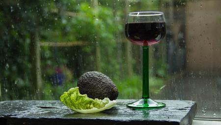 sensation: Summer sensation. Fresh rain in the garden outside, avocado, salad, and a glass of wine on the windowsill Stock Photo