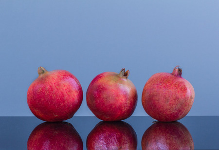Three same large ripe appetizing pomegranate on a blue background and with reflection on a smooth surface