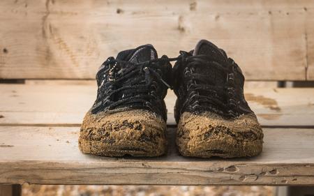 suelo arenoso: Vista frontal del viejo par negro desgastado par de zapatos fiable húmeda son en un banco