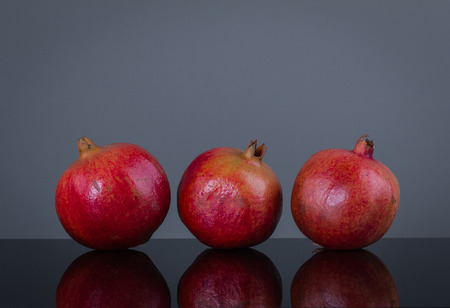 gamme de produit: Three same large ripe appetizing pomegranate on a grey background and with reflection on a smooth surface