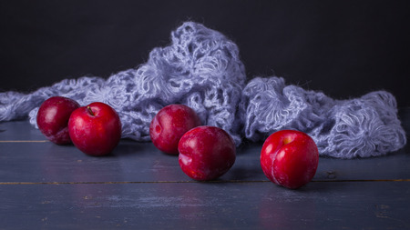 Rijpe rode pruimen met gebreide blauwe wol op de rustieke lijst en de donkere achtergrond