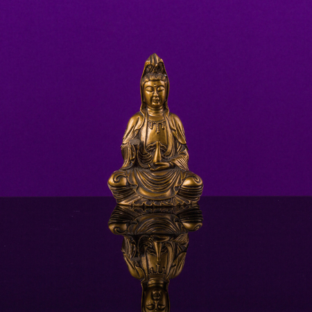 sustained: Buddha of bronz  in meditation on the violet background