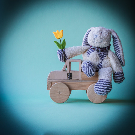 Easter concept with toys. A soft toycheerful rabbit with yellow tulip sitting on the wooden toycar.
