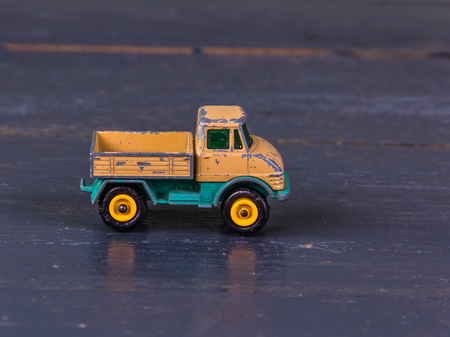 Old, dirty, shabby, model toy of metal, truck in orange close-up on the wooden background. Stock Photo