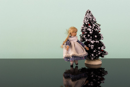glans: Old, antique little doll with Christmas-tree on the glans table Stock Photo