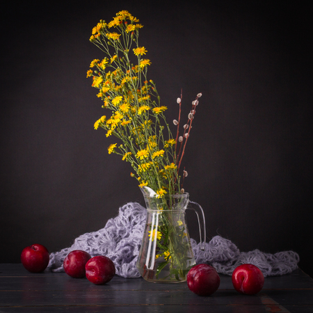 A beautiful still-life with a simple bouquet in a glass jar, large red plums and knitted shawl in the background