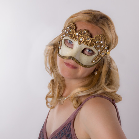Fabulous young blonde with Venetian mask looking at camera