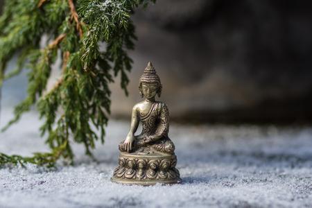 Beeldje van metaal Boeddha en tak van dennenboom in de sneeuw