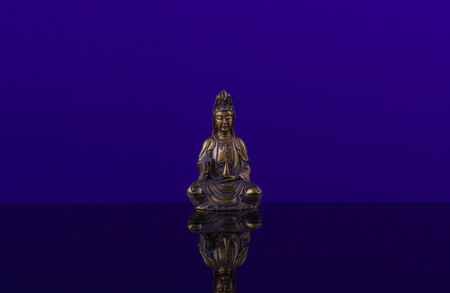 imperturbable: Buddha of bronz in meditation on the beautiful  background of blue cobalt