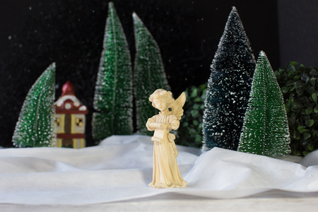 Christmas decor scene with  angel sings Christmas songs on the background of winter forest and  house Stock Photo