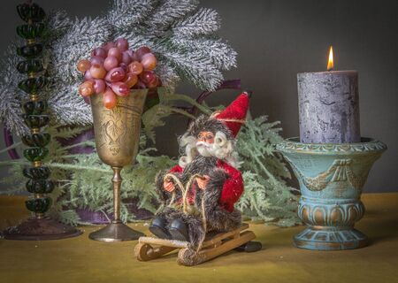 santaclaus: Close-up Christmas decoration on the table with Santa-Claus on sledge, candlestick,  grapes and  branch of christmas tree in snow