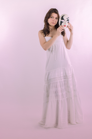 Cute brunette in a long dress  holding a theatrically mask Stock Photo