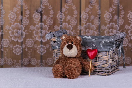 Cute teddy bear is sitting with heart of candy and waiting his beloved.