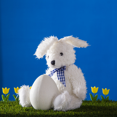 Easter composition with white teddy drear rabbit, five yellow tulips and big egg with craquelure on the blue background.