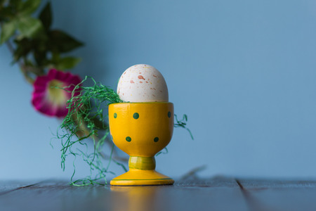 striated: Simple Easter still life with egg in a ceramic yellow dotted bowl.