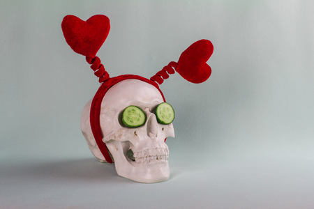 Amusing droll skull with two red hearts and two cucumbers on the soft turquoise background. Stock Photo