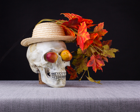 The skull with hat and branch of maple watching  with apple eyes