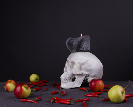 Halloween festival. Still life with skull, candle, apples and red pepper