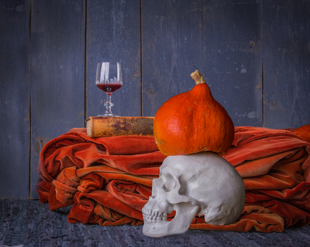 Still life of Halloween with skull, old book, pumpkin and red wine on the gray wooden background Stock Photo