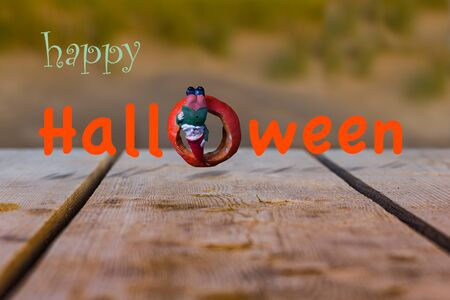 prank: Gnome hangs upside down on a gourd, which is in the form of the letter O Stock Photo