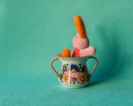 Teddy rabbit on the turquoise background sitting on the  ceramic tableware. Stock Photo