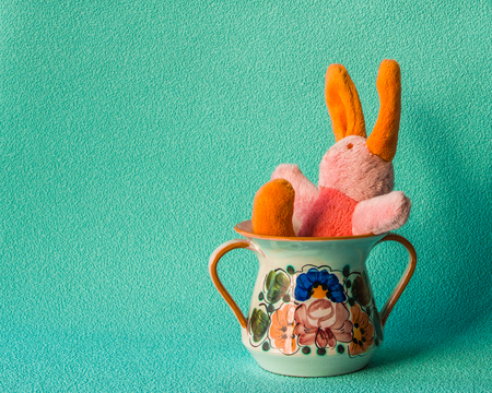 Teddy rabbit on the turquoise background sitting on the  ceramic cream cup.