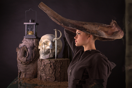 sinful: Halloween scene. Woman in a black dress with organic headdress, tree stump, skull and lamp on a black background Stock Photo