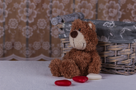 Cute teddy bear is sitting with candy and waiting his beloved.