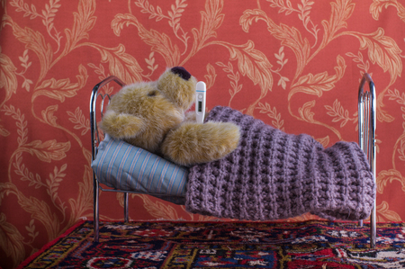 Sick Lonely Teddy Bear Lying With Thermometer In Bed A Room