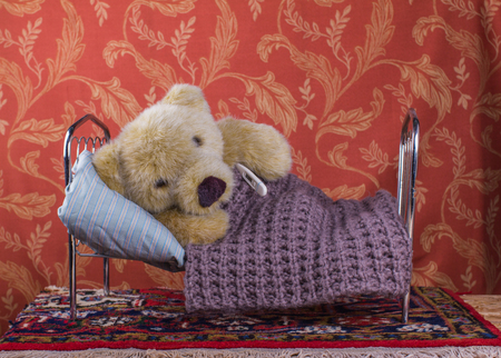 Sick concept. Teddy bear lying  with thermometer in bed home in a room with old fashioned wallpaper and old red carpet Stock Photo