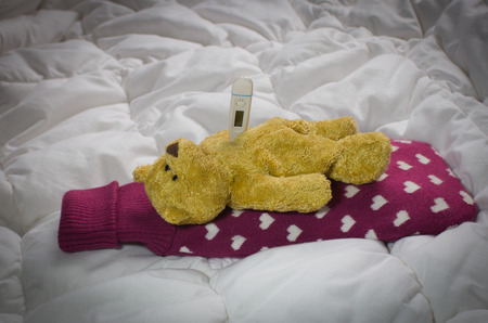 wärmflasche: Sick concept. Teddy bear is lying on a bed with  hot-water bottle and thermometer. He is looking at the ceiling Lizenzfreie Bilder