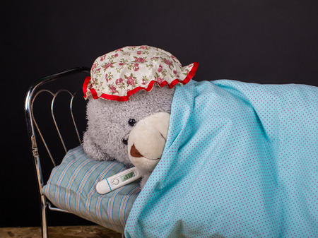 oneself: Sick lonely teddy bear lying  with thermometer in bed  in a room with a black background Stock Photo