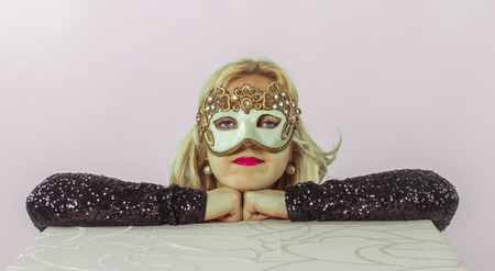 Fabulous young blonde with Venetian mask looking direct at camera
