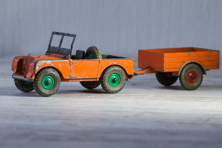 battered land: 3d small retro model of car Land Rover, used, heavy, toy of metal in orange.