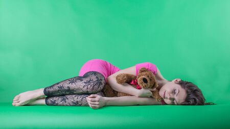 oneself: Rrelax lazy days concept. Weary young femininity woman sleeping with her darling teddy bear on the green background