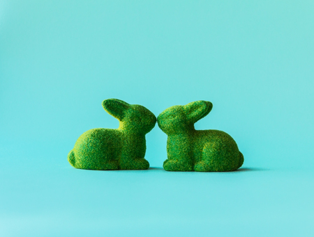 Symbol of Easter, Two green rabbits, in a kiss on the vibrant blue background.