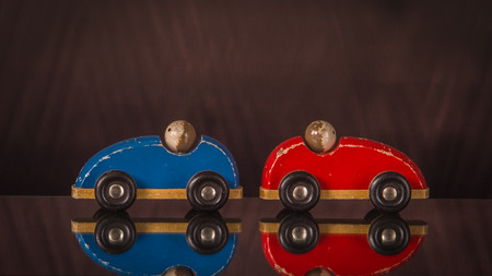 Concept communication and development of child. Two toy cars are in different directions.