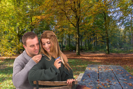 footsie: View of a young attractive couple in a sunny forest with a cup of coffee.