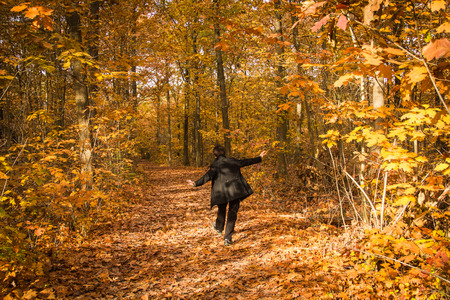 ample: Joyous woman dancing in the path of autumn golden forest