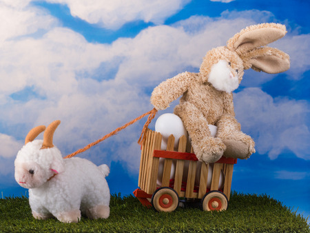 Funny toys bunny and lamb in scene with wooden cart of eggs on the blue sky background. Stock Photo