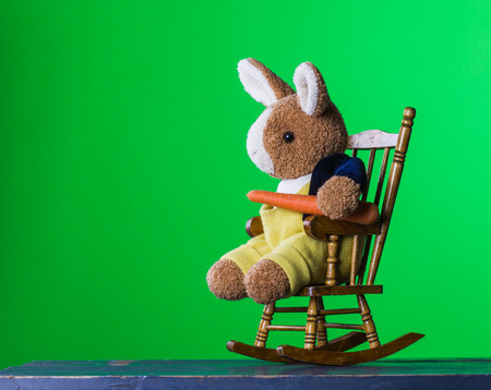 Healthy Easter scene, teddy rabbit sitting on the wooden rocking chair and eating with pleasure carrot, on the green background. Stock Photo