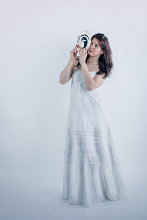 Psychological concept. The girl in a white long dress on a white background is trying to put on a mask Stock Photo