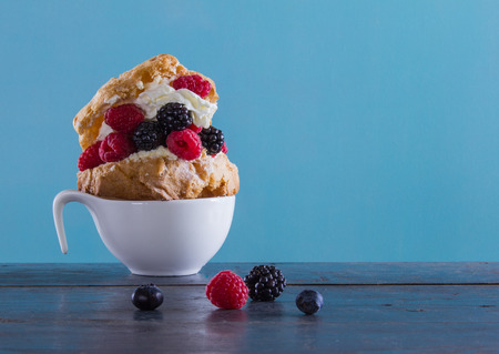 vitamin rich: Delicious dessert with fresh raspberries and blackberries in a puff with whipped cream on the blue background.