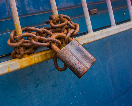 Heavy lattice with a rusty chain lock on the blue background in the perspective, horizontal. Stock Photo