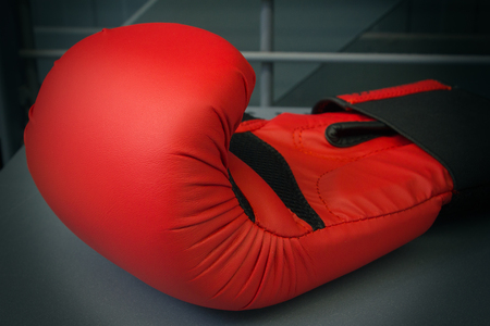 One new boxing glove on the gray background, close-up, horizontal