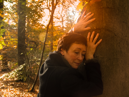 Aged woman touched a large tree in the autumn sunny forest