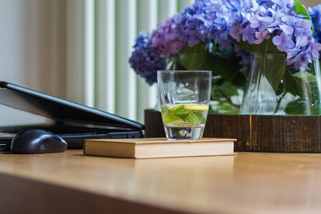 Workplace at home, computer, blue hydrangeas, fresh drink water with mint and lemon, book, light from window.