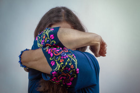 Women hopelessly closed her face with her hands. Despair and social issues concept. Stock Photo